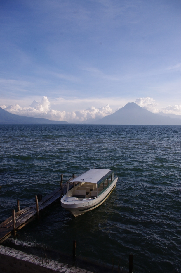 A boat rocks on the choppy waters of Lake Atitlan as it faces the shadow of the nearby volcano.